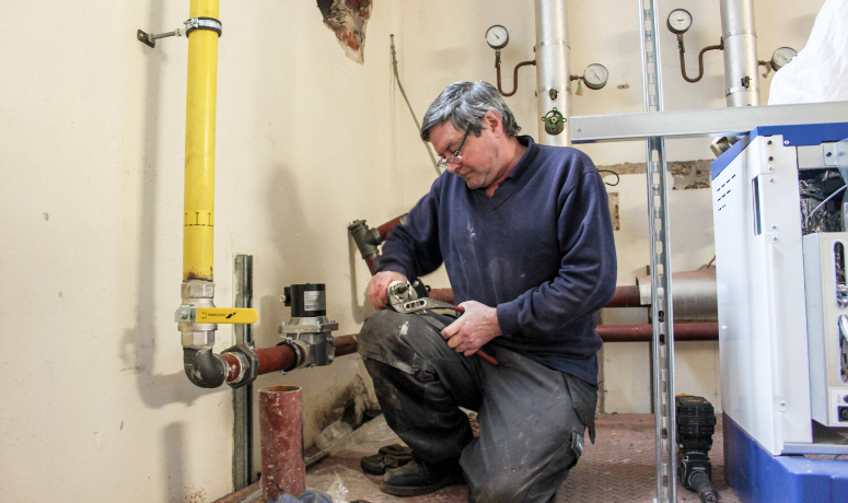 Man carrying out plumbing works - Now is the Time to Undertake Building Maintenance