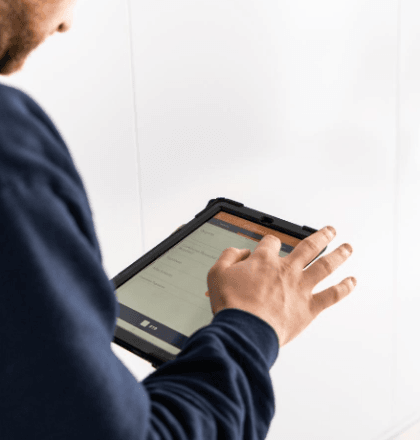 Man on handheld tablet ticking off tasks for Legionella Testing in Schools